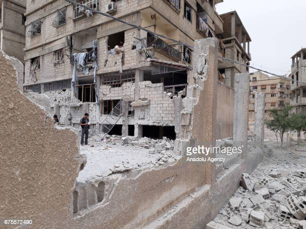 Syrians inspect the debris after Assad Regime's airstrike hit residential areas at the Saqba town of Eastern Ghouta in Damascus Syria on May 1 2017
