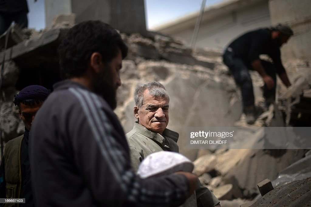Syrians inspect the remains of a destroyed house following an airstrike by the Syrian airforce in the northern Syrian city of Aleppo on April 15, 2013. The conflict in Syria, which is now in its third year, has cost 70,000 lives, according to the United Nations. AFP PHOTO / DIMITAR DILKOFF
