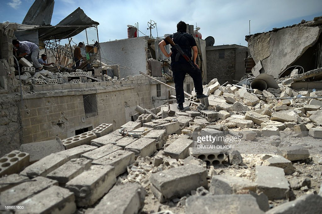 Syrians inspect the remains of destroyed houses following an airstrike by the Syrian airforce in the northern Syrian city of Aleppo on April 15, 2013. The conflict in Syria, which is now in its third year, has cost 70,000 lives, according to the United Nations. AFP PHOTO / DIMITAR DILKOFF