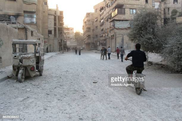 Syrians inspect the site after Assad regime's airstrikes hit residential areas of the deconflict zone in Kafr Batna town of Eastern Ghouta of...