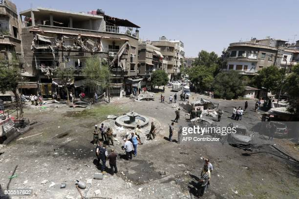 TOPSHOT Syrians inspect the site of a suicide bomb attack in the capital Damascus' eastern Tahrir Square district on July 2 2017 Syrian state...