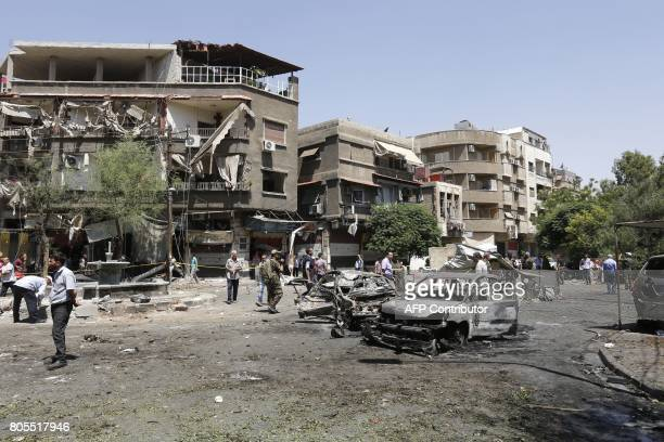 Syrians inspect the site of a suicide bomb attack in the capital Damascus' eastern Tahrir Square district on July 2 2017 Syrian state television...
