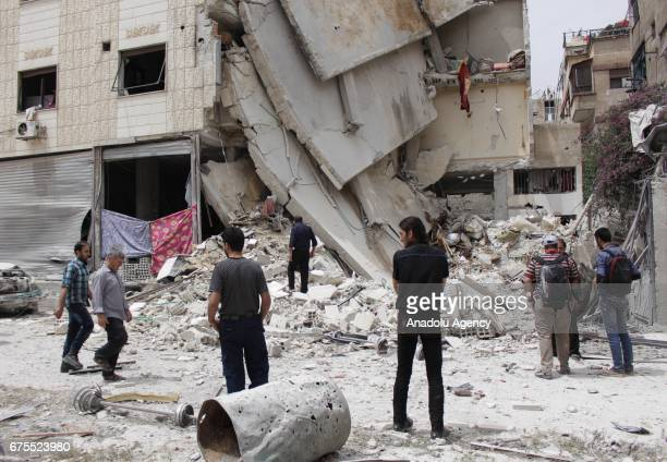 Syrians inspect wreckage of collapsed Arbin hospital after Assad Regime's airstrike hit residential areas at the Arbin district of Eastern Goutha in...