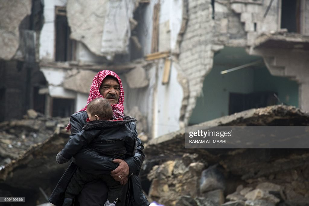 TOPSHOT - Syrians leave a rebel-held area of Aleppo towards the government-held side on December 13, 2016 during an operation by Syrian government forces to retake the embattled city. UN chief Ban Ki-moon expressed alarm over reports of atrocities against civilians Monday, as the battle for Aleppo entered its final phase with Syrian government forces on the verge of retaking rebel-held areas of the city. MASRI