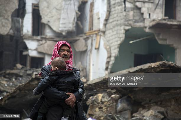 TOPSHOT Syrians leave a rebelheld area of Aleppo towards the governmentheld side on December 13 2016 during an operation by Syrian government forces...