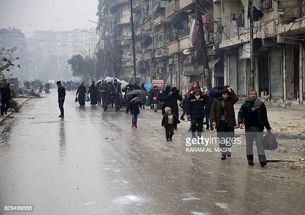 Syrians leave a rebelheld area of Aleppo towards the governmentheld side on December 13 2016 during an operation by Syrian government forces to...