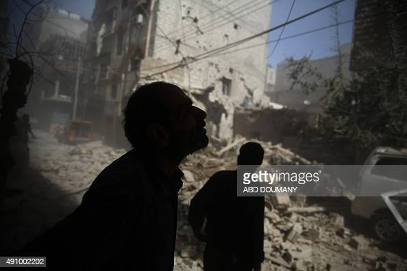 Syrians look at the damage following air strikes on the rebelheld area of Douma east of the capital Damascus on October 2 2015 AFP PHOTO / ABD DOUMANY