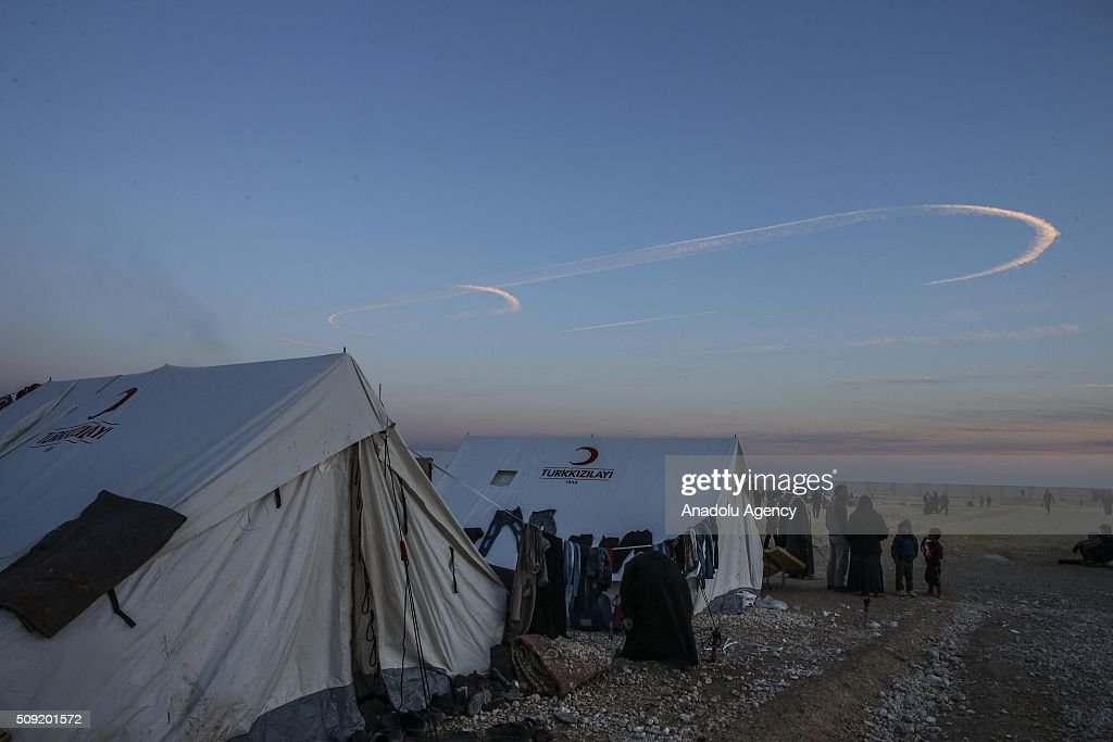 Syrians look at the sky at a tent city near the Bab al-Salam crossing, opposite the Turkish province of Kilis, in Azaz town of Aleppo, Syria as the war crafts belonging to the Russian Army carries out airstrikes on the residential areas on February 9, 2016.