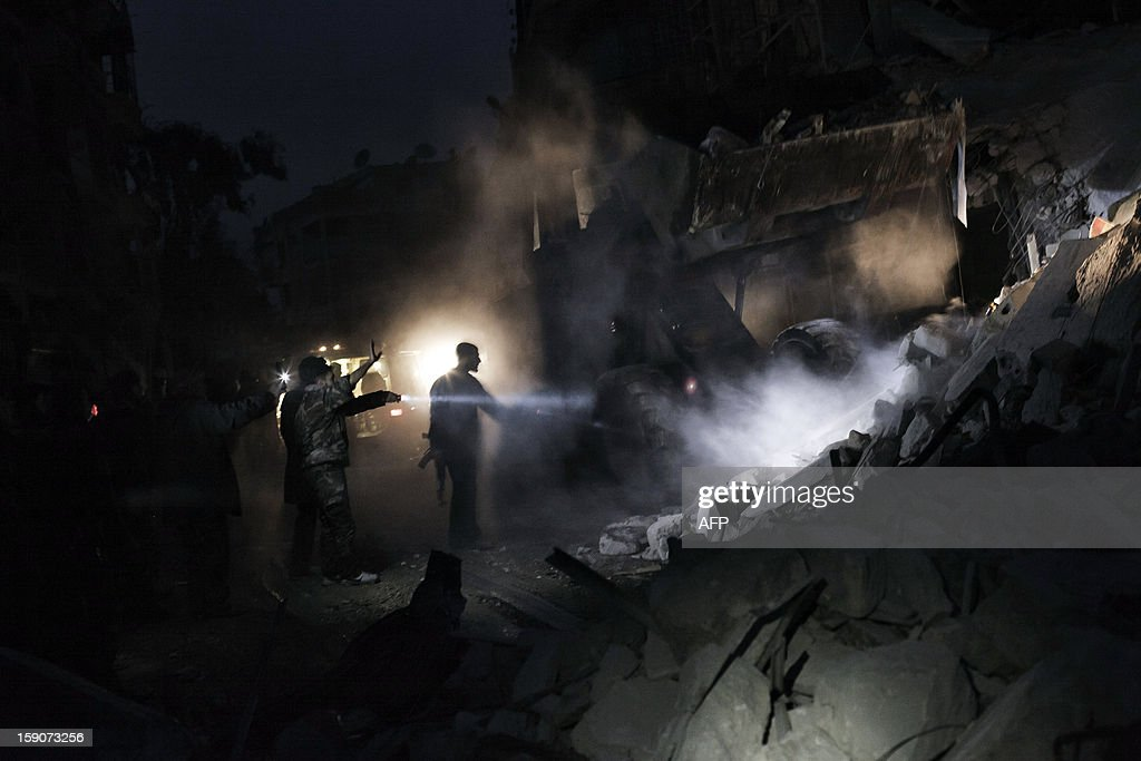 Syrians look for survivors amidst the rubble of a building targeted by a missile in the al-Mashhad neighbourhood of Aleppo on January 7, 2013. The United Nations recently denounced a 'proliferation of serious crimes including war crimes' in Syria, as ever more horrifying images and videos emerge from the country. AFP PHOTO /ACHILLEAS ZAVALLIS