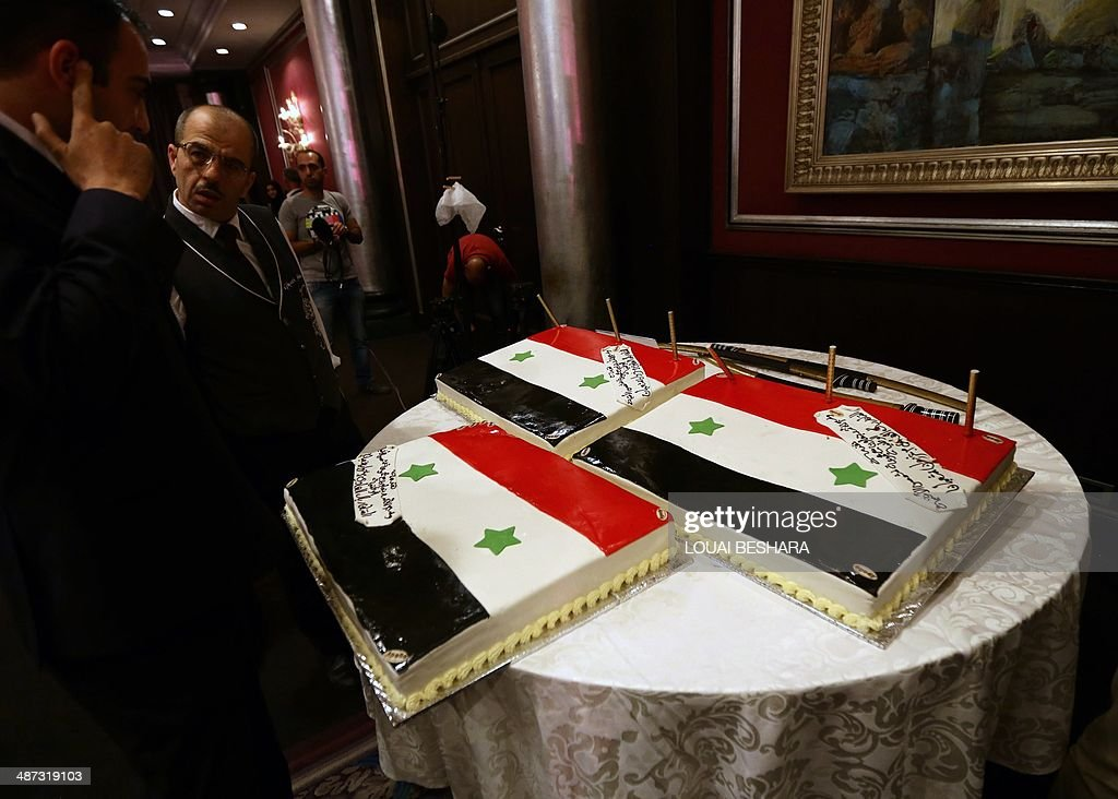 Syrians looks at wedding cakes bearing the colours of their national flag during a reception following a group wedding ceremony consisting of twenty couples made up of government soldiers and their brides in Damascus on April 29, 2014.