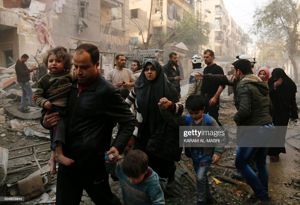 TOPSHOT Syrians make their way through debris as they leave for a safer place following air strikes in the rebelcontrolled side of the northern city...