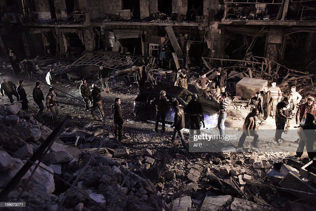 Syrians make their way through the debris after a missile hit a building in the al-Mashhad neighbourhood in the city of Aleppo on January 7, 2013. The United Nations recently denounced a 'proliferation of serious crimes including war crimes' in Syria, as ever more horrifying images and videos emerge from the country.