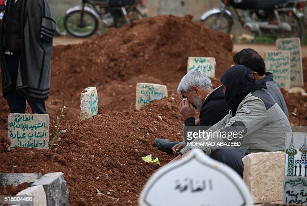 Syrians mourn on the grave of relatives in a rebel held area in the city of Daraa southern Syria on March 29 2016 Syria's conflict has left more than...