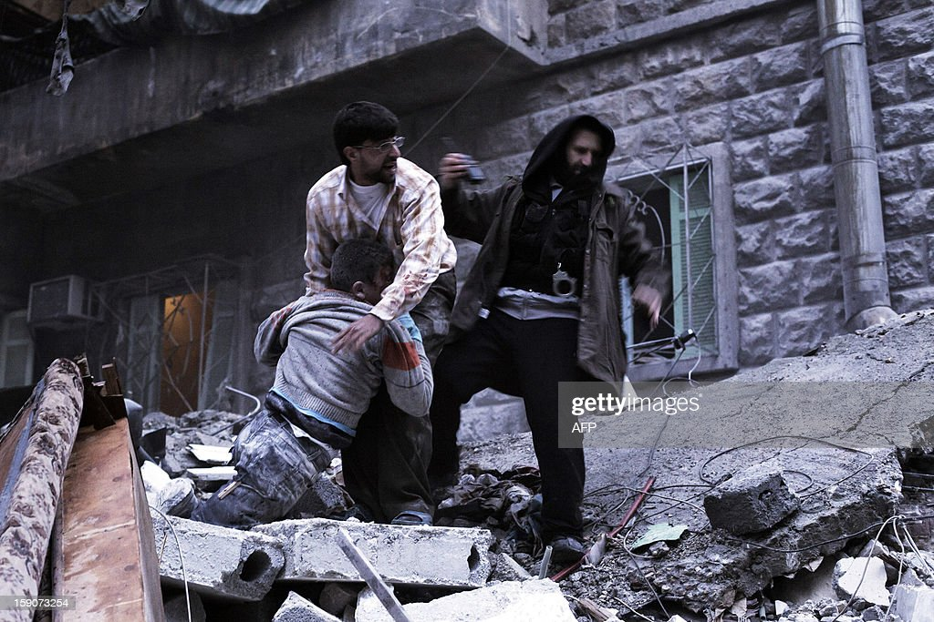 Syrians pull the body of a wounded man from the rubble of a building targeted by a missile in the al-Mashhad neighbourhood in the city of Aleppo on January 7, 2013. The United Nations recently denounced a 'proliferation of serious crimes including war crimes' in Syria, as ever more horrifying images and videos emerge from the country. AFP PHOTO / ACHILLEAS ZAVALLIS