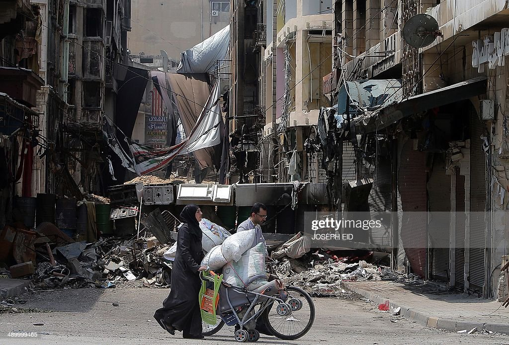 Syrians push a puschair and a bike loaded with their belongings as anti-sniper curtains remain in a street on May 12, 2014 in a destroyed neighbourhood of the Old City of Homs, some 162 kilometres north of the capital Damascus. Syrians have been streaming back into the ruins of the Old City of Homs since May 10, 2014, picking through the remains of their homes and trying to come to terms with the destruction.