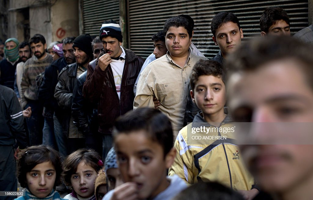 Syrians queue up to buy bread outside a bakery in the al-Fardos neighbourhood of the northern Syrian city of Aleppo on December 9, 2012. The cost of basic commodities such as bread and fuel are rising in the city as Syrians have been struggling to continue their daily lives without water or electricity for one week now. AFP PHOTO / ODD ANDERSEN