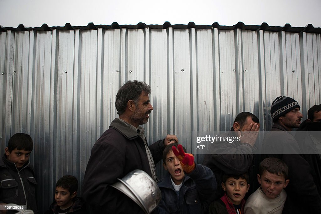Syrians queue up to receive food rations at a refugee camp near the northern city of Azaz on the Syria-Turkey border, home to more than 7000 people mostly from the northern districts of Aleppo and Marea, on January 8, 2013. The internally displaced faced further misery due to increasing shortage of supplies as heavy rain was followed by a drop in temperatures.