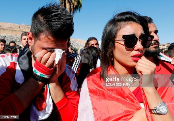 Syrians react after their national team lost to Australia in the World Cup qualifying playoff football match as they gathered at the Umayyad Square...