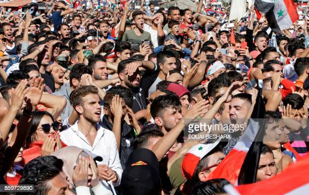 Syrians react while cheering on their national team at the Umayyad Square in Damascus as they watch a live broadcast of the World Cup 2018 qualifying...