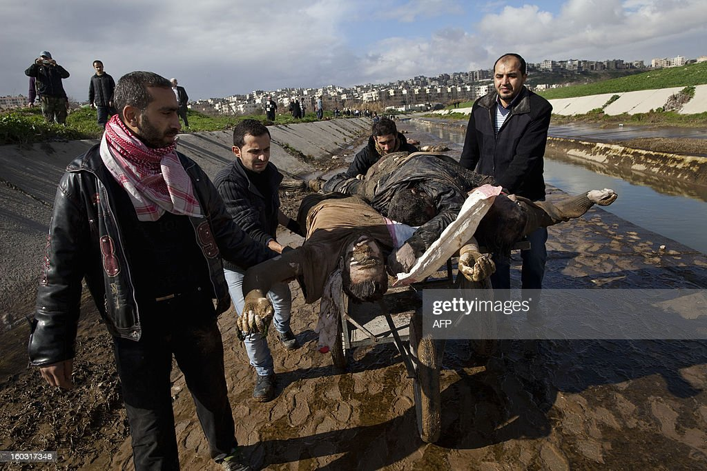 Syrians recover the bodies of executed men along a canal in the northern city of Aleppo before transferring the corpses to a hospital where relatives could seek to identify them on January 29, 2013. The bodies of at least 68 unidentified young men and boys, all executed with a single gunshot to the head or neck, were found in the Quweiq River, which separates the Bustan al-Qasr district from Ansari in the southwest of Aleppo, in a rebel-held area where a Free Syrian Army captain said many more were still being dragged from the water.