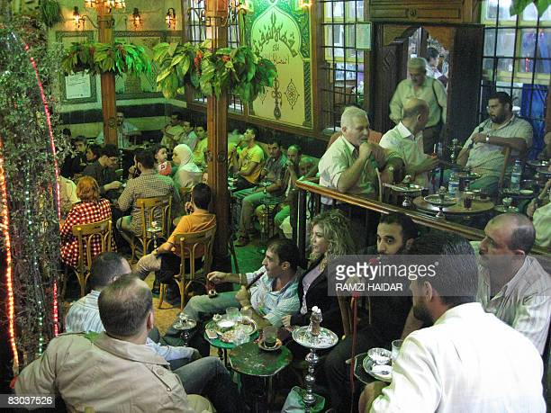 Syrians relax and smoke waterpipes in a cafe late on September 27 in old Damascus following a deadly morning bomb blast in the downtown area of the...