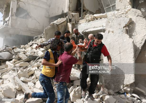 Syrians remove a victim from the rubble of a destroyed building following a reported air strike in the Qatarji neighbourhood of the northern city of...