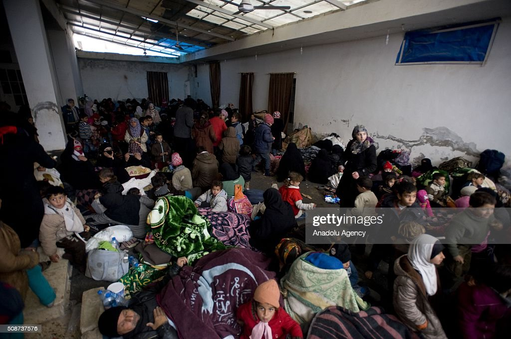 Syrians rest in a camp built by IHH Humanitarian Relief Foundation near Bab al-Salam border gate on Turkey's border in Azez district of Aleppo as they flee to Turkey to escape heavy Syrian regime and Russian airstrikes, on February 6, 2016.
