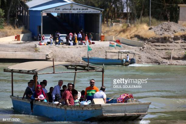 Syrians ride a boat after crossing the Tigris river to head back to Syria's Kurdish area from Iraqi Kurdistan through the Semalka border crossing in...