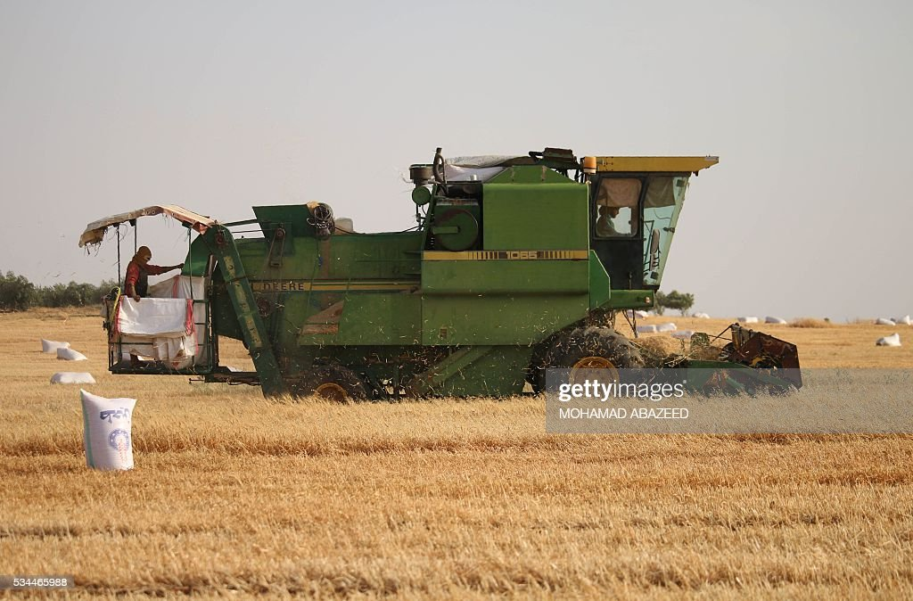 Syrians ride a combine harvester as they harvest wheat in rebel-held area of Daraa, in southern Syria, on May 26, 2016. Most of Daraa province is controlled by opposition forces, though the government holds parts of the provincial capital and a few villages in the northwest. ABAZEED