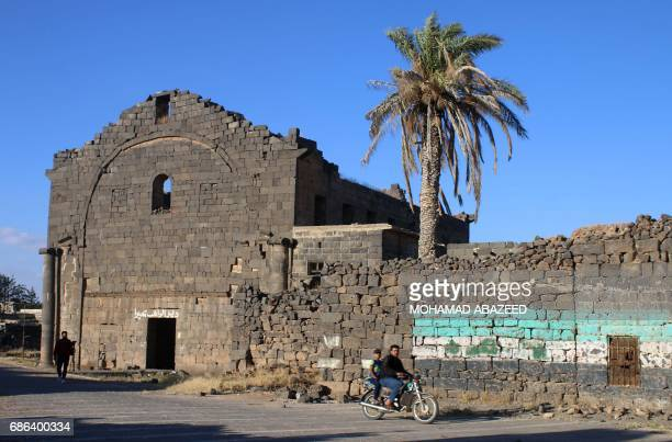 Syrians ride a motobike past the Rahib Buhayra Monastery in the ancient city of Bosra alSham which is listed as a UNESCO World heritage site in the...