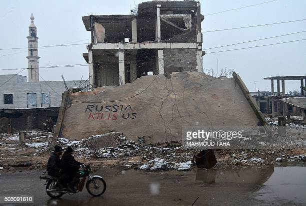Syrians ride a motorbike past a collapsed building on which a graffiti reads 'Russia kills us' on January 1 2016 in the central Syrian town of...