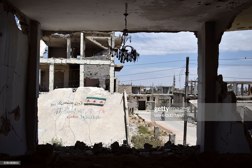 Syrians ride a motorbike past a collapsed building on which a graffiti reads 'Save Aleppo' on April 30, 2016 in the central Syrian town of Talbisseh in the Homs province. / AFP / MAHMOUD