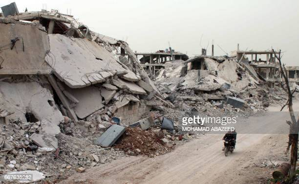 TOPSHOT Syrians ride a motorcycle amid the destruction in a rebelheld neighbourhood in the rebelheld area of Daraa in southern Syria on April 12 2017...