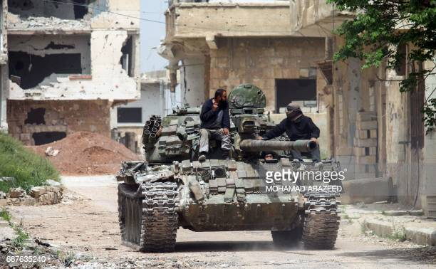 Syrians ride on the turret of a moving tank in the rebelheld area of Daraa in southern Syria on April 12 2017 / AFP PHOTO / MOHAMAD ABAZEED