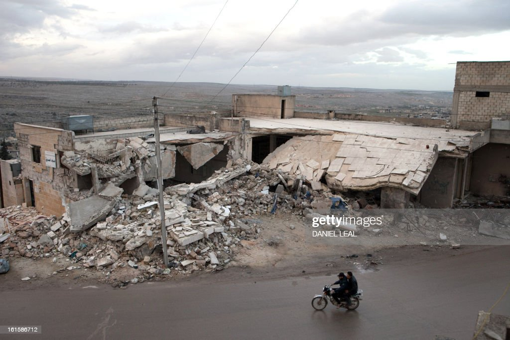 Syrians ride on their motorcycle past the remains of a building allegedly destroyed by an explosive device dropped from a Syrian jet fighter in the town of Kfar Nubul, in the northwestern province of Idlib, on February 11, 2013. UN Secretary General Ban Ki-moon on Monday urged the Syrian government of President Bashar al-Assad to accept an offer by the head of the opposition coalition for peace talks.