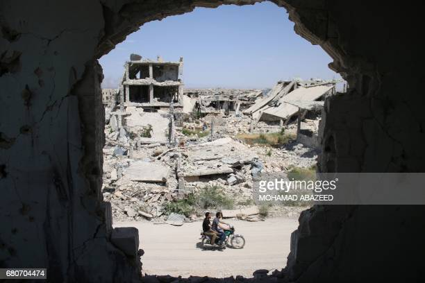 TOPSHOT Syrians rides a motorbike past destroyed buildings in a rebelheld area of the southern city of Daraa on May 9 2017 / AFP PHOTO / Mohamad...