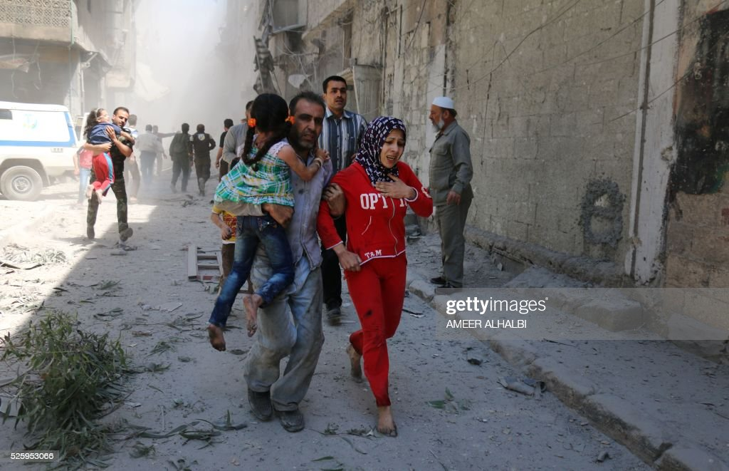 Syrians run for cover amid the rubble of destroyed buildings following a reported air strike on the rebel-held neighbourhood of Al-Qatarji in the northern Syrian city of Aleppo, on April 29, 2016. Fresh bombardment shook Syria's second city Aleppo, severely damaging a local clinic as outrage grows over an earlier air strike that destroyed a hospital. The northern city has been battered by a week of air strikes, rocket fire, and shelling, leaving more than 200 civilians dead across the metropolis. The renewed violence has all but collapsed a fragile ceasefire deal that had brought an unprecedented lull in fighting since February 27. / AFP / AMEER
