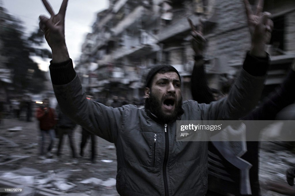 Syrians rush to the location of a building targeted by a missile in the al-Mashhad neighbourhood in the city of Aleppo on January 7, 2013. The United Nations recently denounced a 'proliferation of serious crimes including war crimes' in Syria, as ever more horrifying images and videos emerge from the country. AFP PHOTO / ACHILLEAS ZAVALLIS