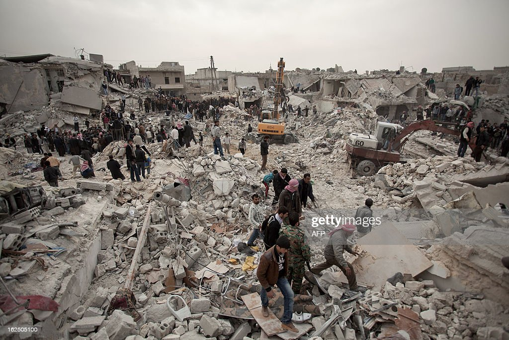 Syrians search for survivors and bodies amid the rubble of buildings in the Tariq al-Bab district of the northern city of Aleppo on February 23, 2013. Three surface-to-surface missiles fired by Syrian regime forces in Aleppo's Tariq al-Bab district have left 58 people dead, among them 36 children, the Syrian Observatory for Human Rights said on February 24. AFP PHOTO/PABLO TOSCO