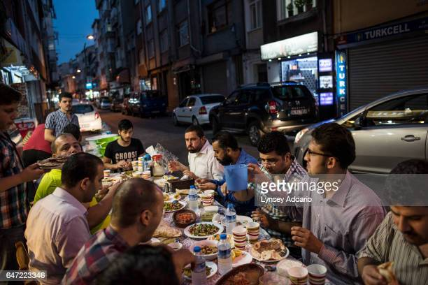 Syrians share an Iftar dinner in front of the El Nour Syrian sweets shop along Naci Professor Sensoy Avenue in the Fatih neighbourhood in Istanbul...