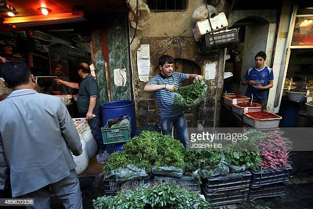 Syrians shop at vegetable market in Damascus on September 23 2015 as Muslims prepare to celebrate the holiday of Eid alAdha or Feast of the Sacrifice...