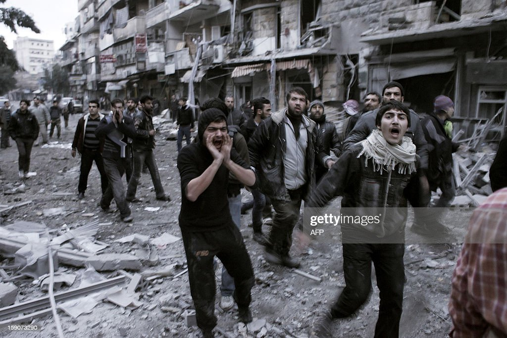 Syrians shout slogans as they rush to the location of a building targeted by a missile in the al-Mashhad neighbourhood of Aleppo on January 7, 2013. The United Nations recently denounced a 'proliferation of serious crimes including war crimes' in Syria, as ever more horrifying images and videos emerge from the country. AFP PHOTO / ACHILLEAS ZAVALLIS