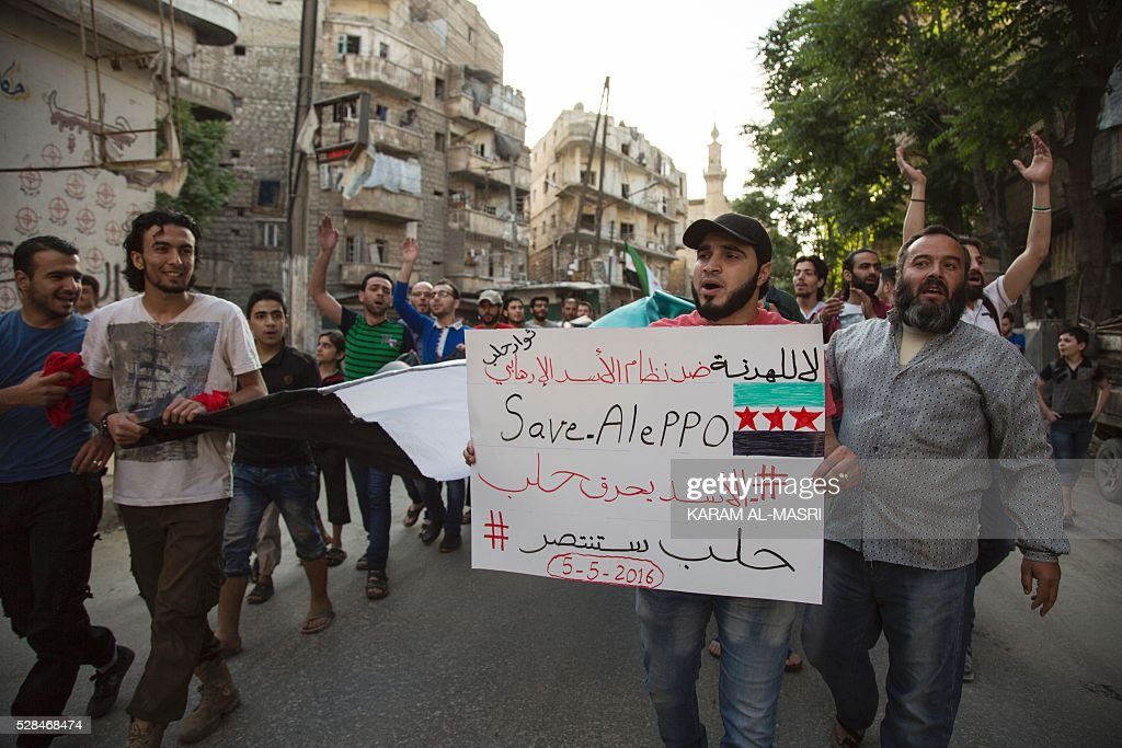 Syrians shout slogans during an anti-regime protest in the rebel-held Bustan al-Qasr district in eastern Aleppo on May 5, 2016. The Syrian army said late on May 4 that it had agreed to calls from Russia and the United States for a two-day truce in Aleppo that would begin from 1:00 am on May 5. Renewed fighting in recent days, especially in and around Aleppo, had threatened the full collapse of the February 27 ceasefire agreement, a landmark in attempts to finally resolve a conflict that has left more than 270,000 dead. / AFP / KARAM