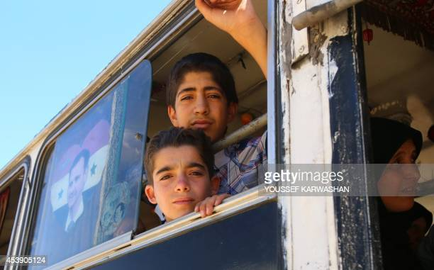 Syrians sit on a bus heading to the southern Damascus district of Qadam on August 21 as they return to their homes after Syrian authorities and...