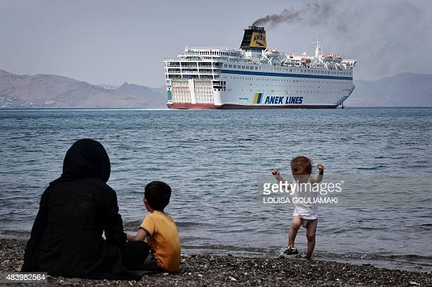 Syrians sitting on the beach watch the Eleftherios Venizelos ferry which will be hosting an accomodation and registration centre for migrants...