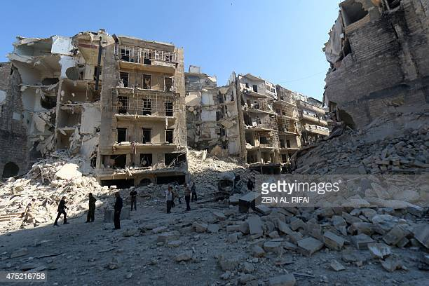 Syrians stand amidst the destruction in the eastern Shaar neighbourhood of the northern Syrian city of Aleppo on May 30 2015 Once Syria's commercial...