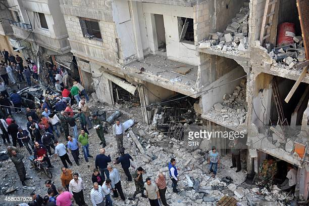 Syrians stand at the site of a car bomb explosion in the alZahraa neighborhood in Homs on October 29 2014 At least 37 people including children were...