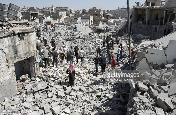 Syrians stand on the rubble of buildings after a missile fired by Syrian government forces hit a residential area in the Maghayir district in the old...