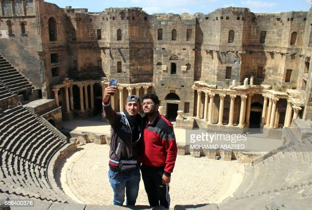 Syrians take a selfie in the ancient Roman amphitheatre of Bosra alSham which is listed as a UNESCO World heritage site in the southern Syrian...