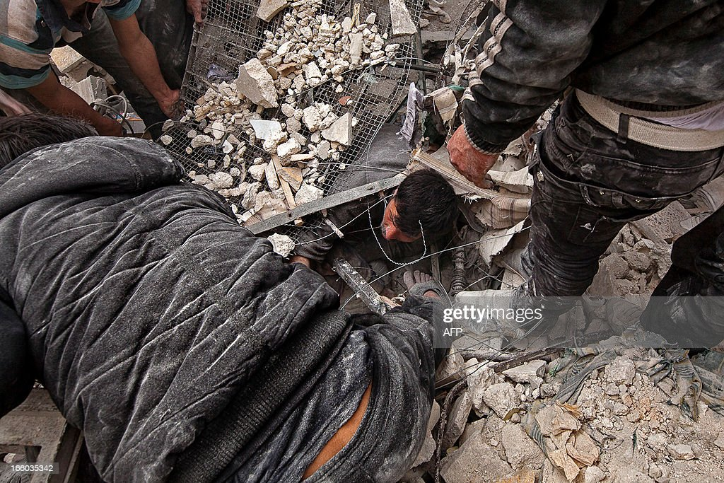 Syrians try to free a man trapped under the rubble following an air strike by government forces on April 7, 2013 that destroyed two five-storey apartment blocks and severely damaged ten buildings in a residential neighbourhood of the northern Syrian city of Aleppo, according to eyewitnesses. Warplanes also raided Yabrud near Damascus and Qusayr in the central province of Homs, as tanks shelled rebel enclaves in Homs city the same day.